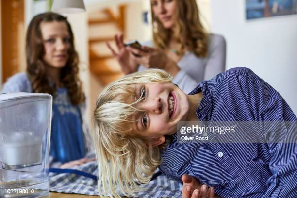 Portrait of grinning blond boy with family in background