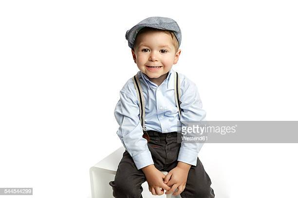 Portrait of grinning little boy wearing cap and suspenders