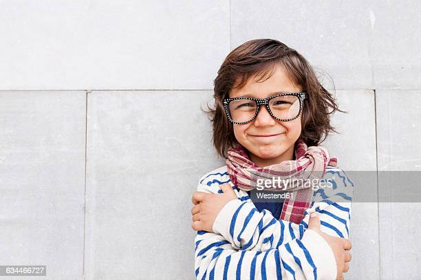 Portrait of grinning little boy wearing scarf and oversized glasses