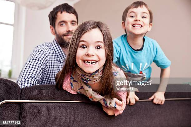 Portrait of grinning little girl at home with father and brother in the background