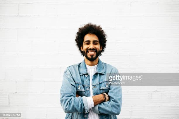 portrait of grinning young man in front of white wall - afro frisur stock-fotos und bilder