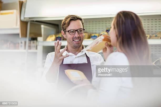 portrait of grocer serving customer in a farm shop - klanten georiënteerd stockfoto's en -beelden