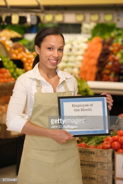 Portrait of grocery employee holding employee of the month plaque