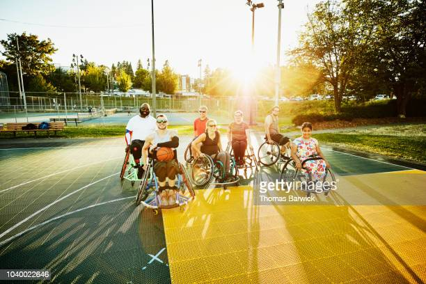 Portrait of group of adaptive athletes on outdoor basketball court after practice on summer evening