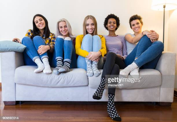 portrait of group of female friends sitting on sofa in living room - five people stock pictures, royalty-free photos & images