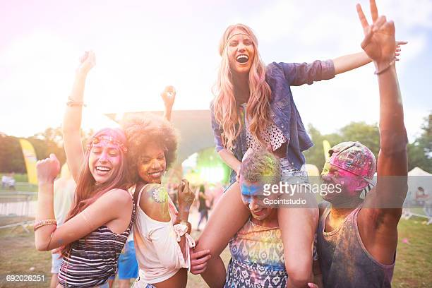 Portrait of group of friends at festival, covered in colourful powder paint