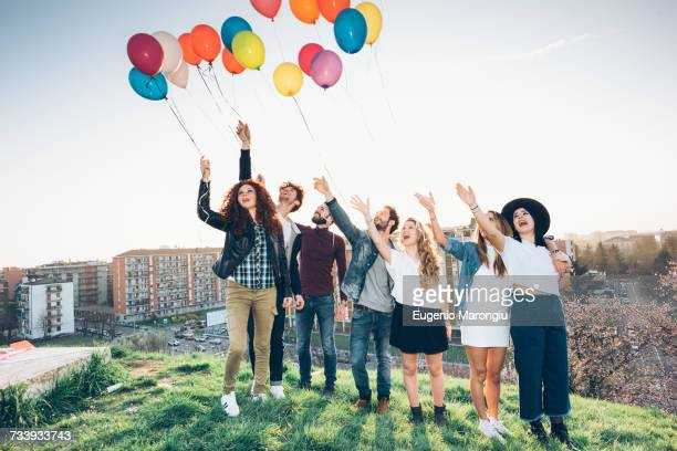 portrait of group of friends, standing on roof, holding helium balloons - releasing stock pictures, royalty-free photos & images