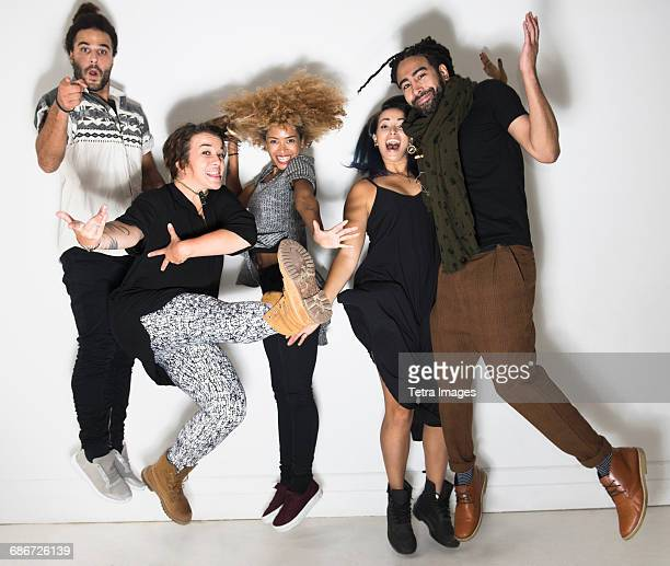 Portrait of group of happy friends against white wall jumping