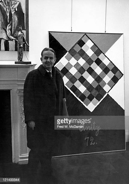 Portrait of Guatamalanborn American painter Alfred Jensen as he poses beside one of his paintings New York New York March 2 1963