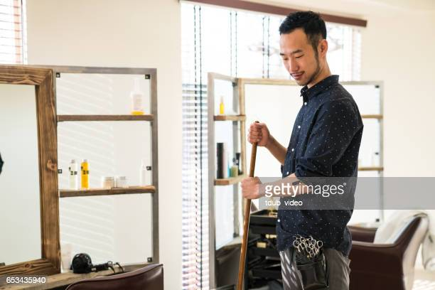 portrait of hairdresser with broom in his small business salon - tdub_video stock pictures, royalty-free photos & images
