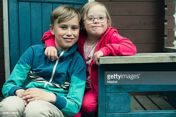 Portrait of handicapped girl with arm around brother sitting on porch