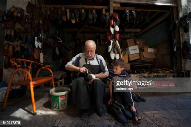 portrait of handmade shoe maker and his little assistant - shoemaker stock photos and pictures