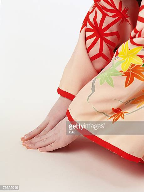 Portrait of hands of a Kabuki actor acting as female sitting down and bowing, High Angle View