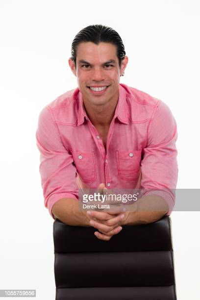 Portrait of handsome adult male in his 30s leaning on desk chair and smiling'n
