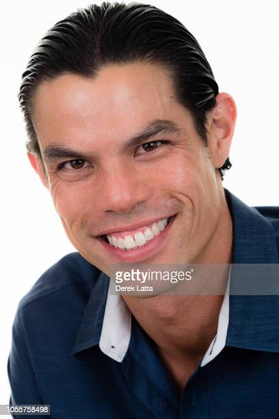 Portrait of handsome Asian-Hispanic man in his 30s looking and smiling at camera'n