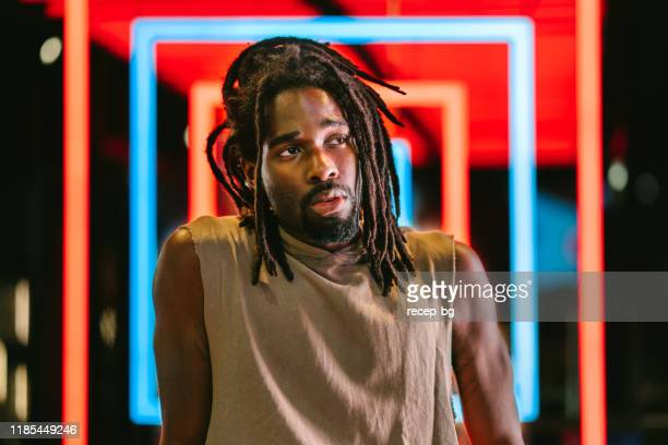 portrait of handsome black man in front of colorful neon lights - hip hop music stock pictures, royalty-free photos & images