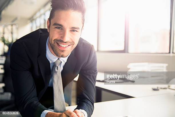 Portrait of handsome businessman leaning at table