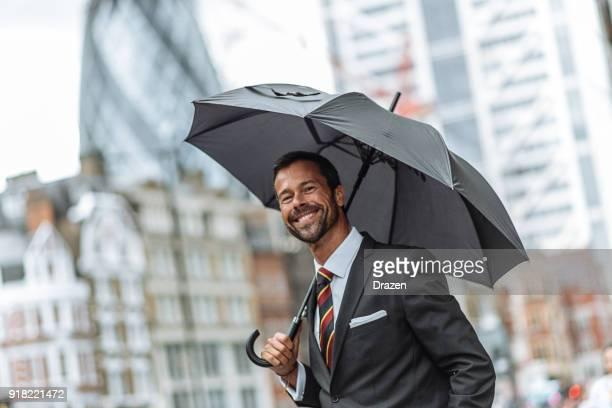 Porträt der schönen Geschäftsmann mit Regenschirm an regnerischen Tag in London