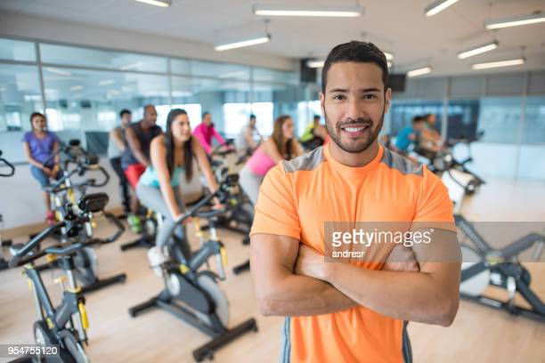 retrato de instrutor de fiação bonito olhando para a câmera com os braços cruzados e classe atrás nas bicicletas estacionárias - instrutor - fotografias e filmes do acervo
