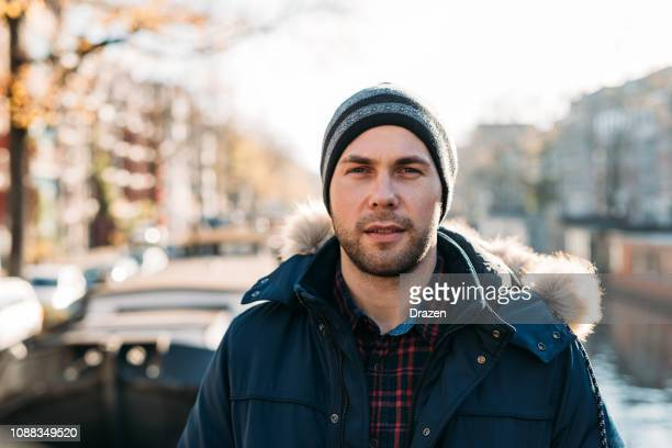 portrait of handsome guy in winter in amsterdam near canal - eastern european descent stock pictures, royalty-free photos & images