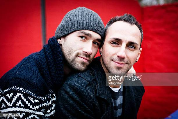 Portrait of handsome homosexual couple in front of red wall