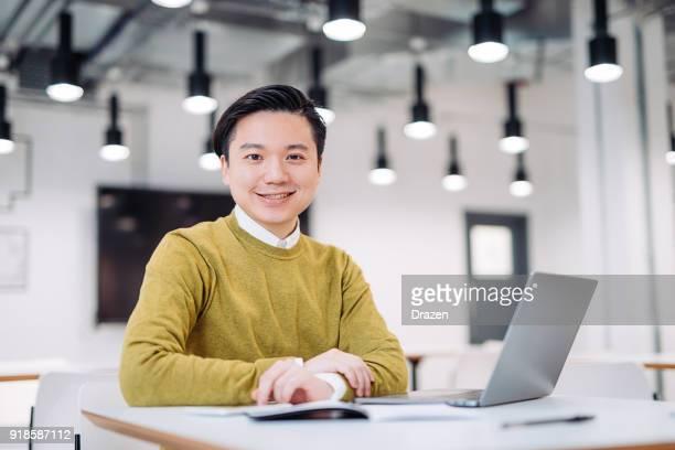 Portrait of handsome Korean entrepreneur working on social media platforms
