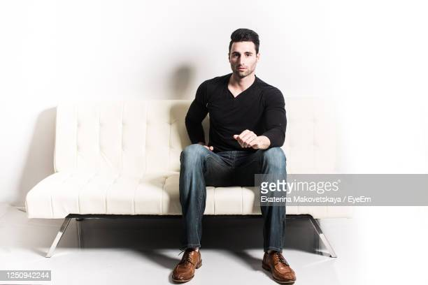 portrait of handsome man sitting on sofa against white background - sitting stock pictures, royalty-free photos & images