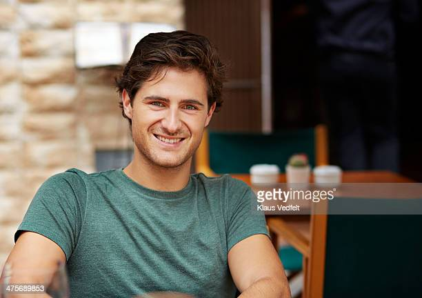 portrait of handsome man smiling at cafe - klaus vedfelt mallorca stock pictures, royalty-free photos & images