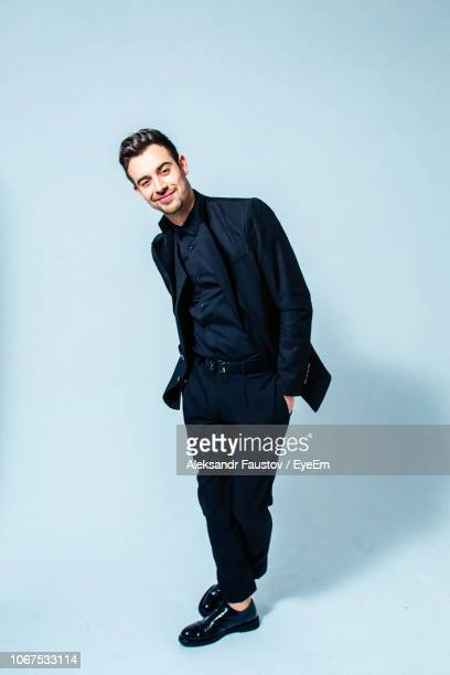 portrait of handsome man standing against blue background - de corpo inteiro imagens e fotografias de stock
