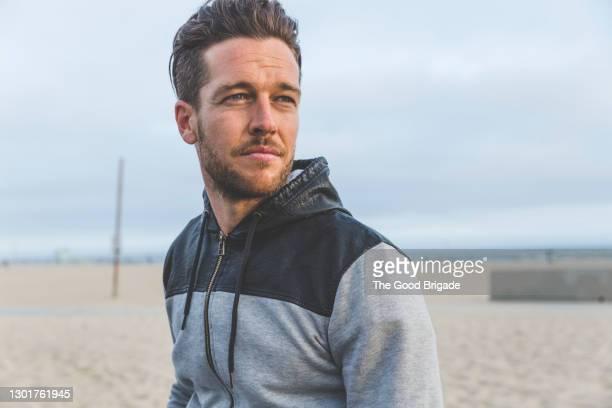 portrait of handsome man standing at beach - knappe man stockfoto's en -beelden
