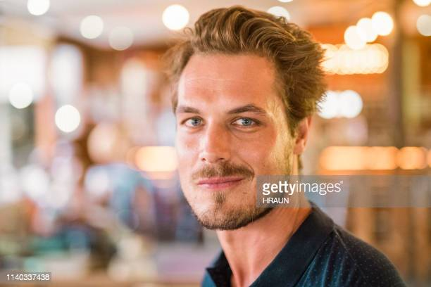 portrait of handsome man standing at restaurant - gray eyes stock pictures, royalty-free photos & images