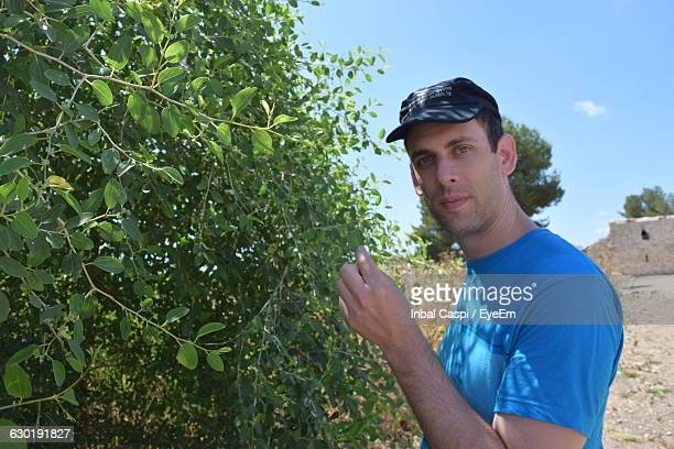 Portrait Of Handsome Man Standing By Plants Against Sky
