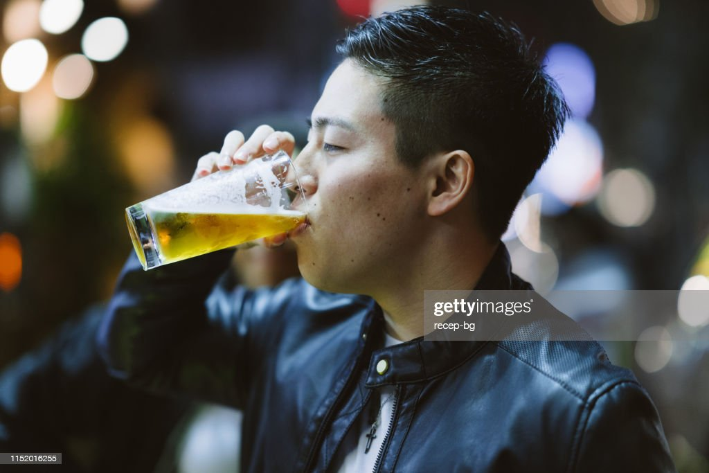 Portrait of handsome man while drinking beer at night : Stock Photo