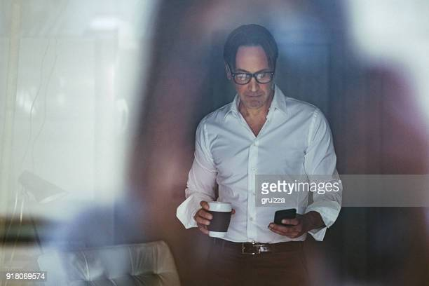 Portrait of handsome mature businessman having coffee and using mobile phone inside modern office space