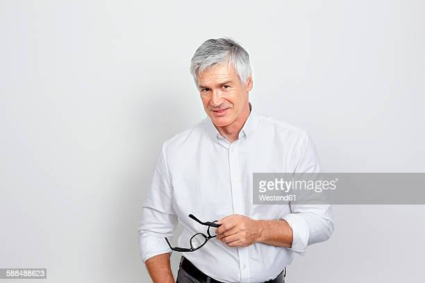 Portrait of handsome mature man holding glasses in his hand