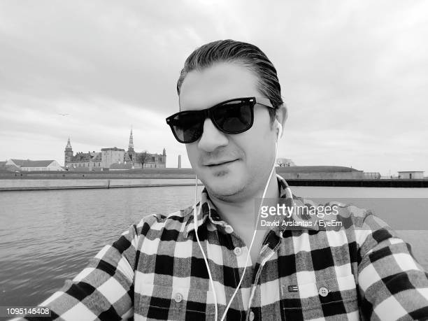 portrait of handsome mature man wearing sunglasses at harbor - helsingor stock pictures, royalty-free photos & images