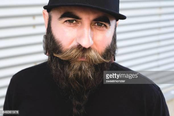 Porträt der gutaussehende Männer mit Schnurrbart und geflochtenen Bart tragen schwarze Kappe und Ohren Tunnel