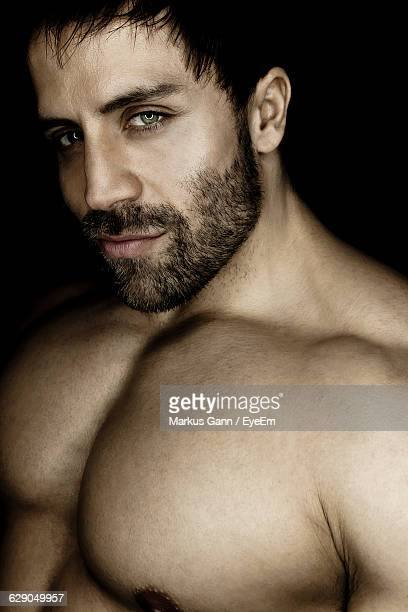 Portrait Of Handsome Shirtless Muscular Man Against Black Background