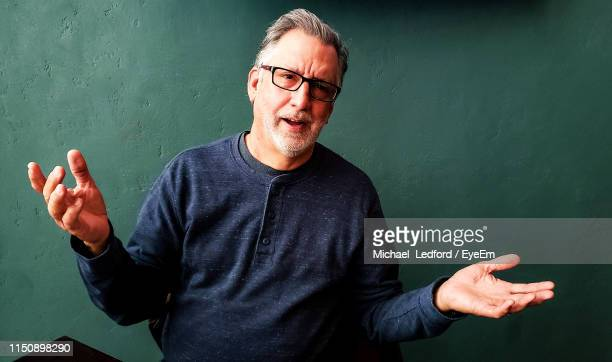 portrait of handsome teacher gesturing standing against wall - gesturing stock pictures, royalty-free photos & images
