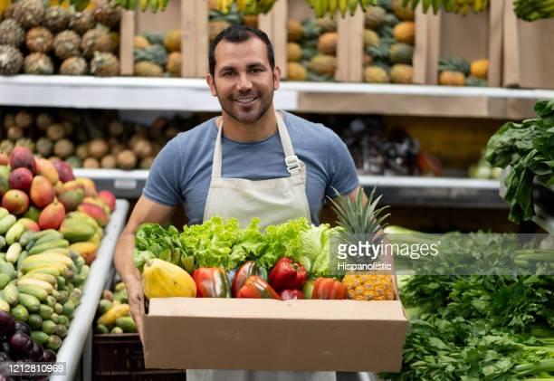 portrait of handsome worker at a farmer's market holding products in cardboard box while facing camera smiling - banca de mercado imagens e fotografias de stock