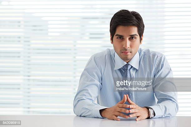 Portrait of handsome young businessman sitting in office
