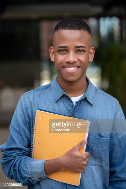 portrait of handsome young college student holding his notebook while facing camera smiling - hispanolistic stock photos and pictures
