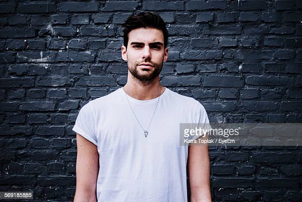 Portrait of handsome young man against stone wall