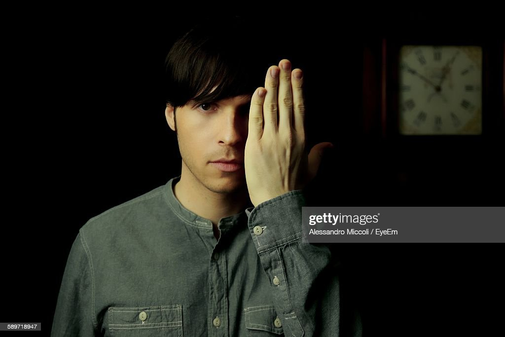 Portrait Of Handsome Young Man Covering Face With Hand : Stock Photo