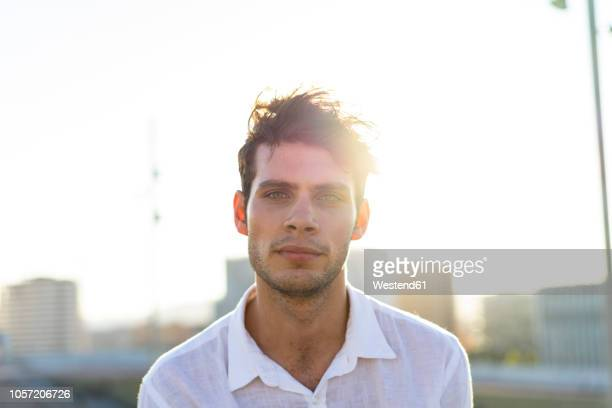 portrait of handsome young man outdoors at sunset - stoppelbart stock-fotos und bilder