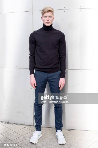 portrait of handsome young man standing against wall - turtleneck stock pictures, royalty-free photos & images