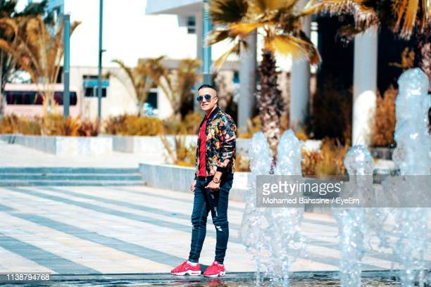 portrait of handsome young man standing by fountain in city - homme marocain photos et images de collection