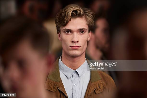 Portrait of handsome young man standing in crowd