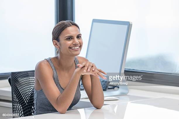 Portrait of happy Aboriginal Australian businesswoman sitting at desk