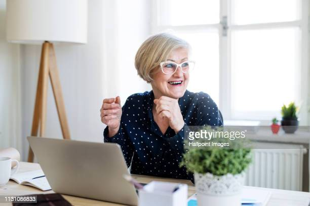A portrait of happy active senior woman with laptop working in home office, laughing.